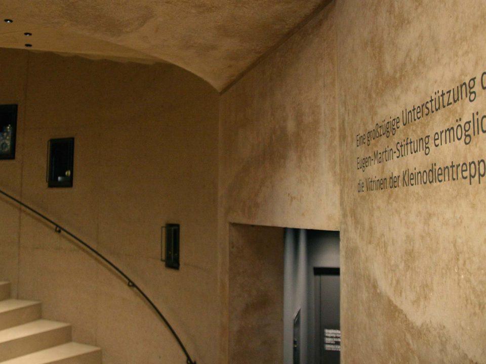"""Aufgang Kleinodientreppe, Schrift an der Wand: """"Eine großzügige Unterstützung der Eugen-Martin-Stiftung ermöglichte die Vitrinen der Kleinodientreppe."""""""